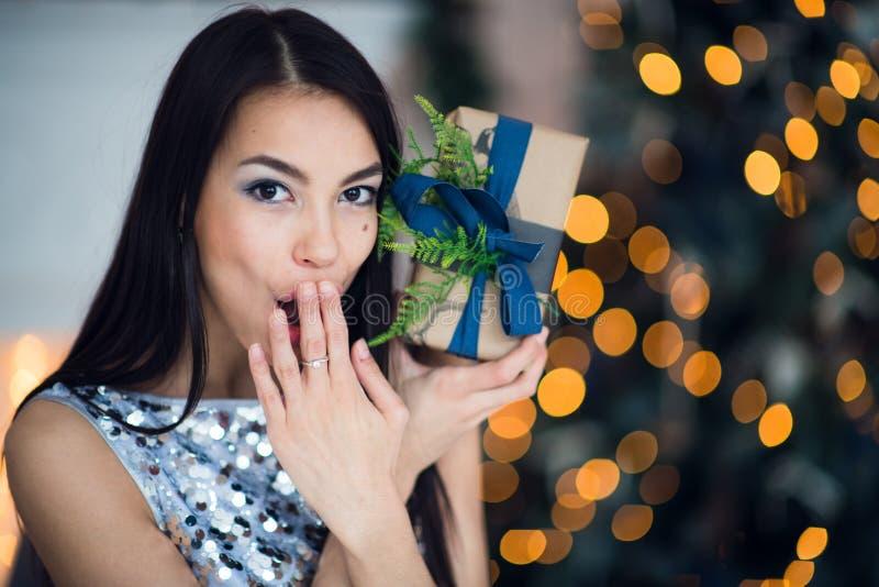 快活庆祝的圣诞节 坐在圣诞树附近的一件惊人的礼服的美丽的妇女 圣诞节奇迹 库存照片