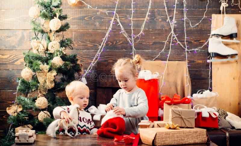 快活的圣诞节节日快乐 偷看从后面圣诞树的微笑的孩子在客厅 逗人喜爱的子项一点 免版税图库摄影