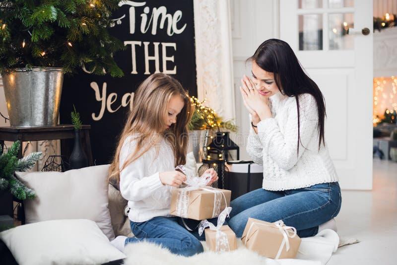快活的圣诞节节日快乐 快乐的妈妈和她逗人喜爱的打开圣诞节礼物的女儿女孩 父母和 库存图片