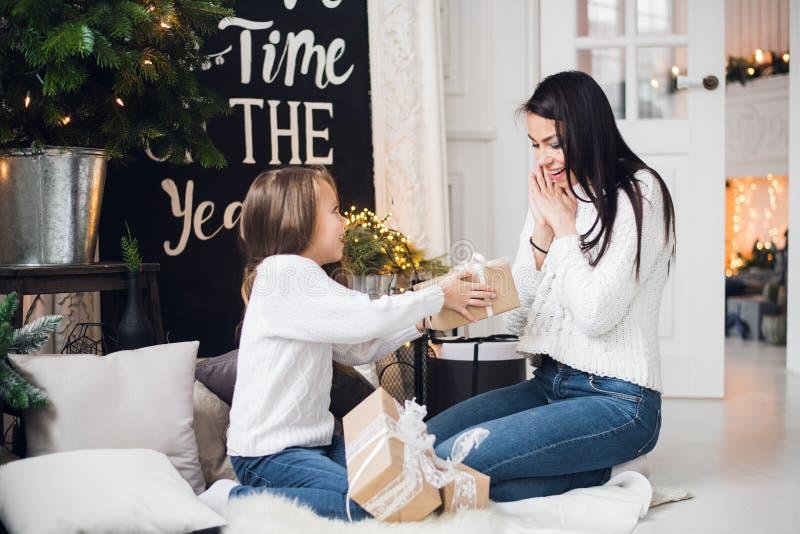 快活的圣诞节节日快乐 快乐的妈妈和她逗人喜爱的打开圣诞节礼物的女儿女孩 父母和 免版税库存照片