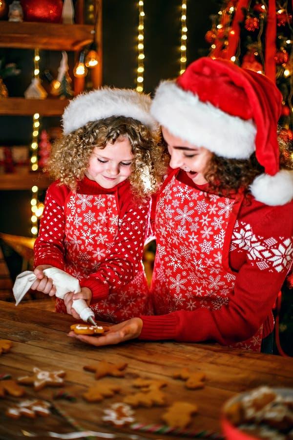 快活的圣诞节节日快乐 快乐的逗人喜爱的卷曲女孩和她的姐姐圣诞老人帽子烹调的 免版税库存照片