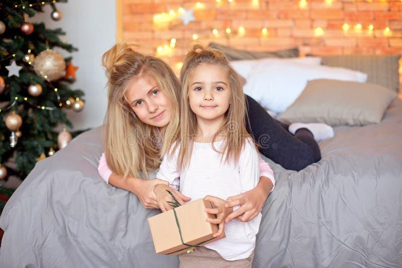 快活的圣诞节节日快乐 打开礼物的快乐的逗人喜爱的孩子 孩子获得乐趣在树附近早晨 免版税库存图片