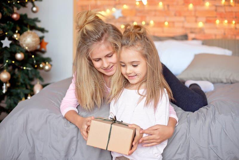快活的圣诞节节日快乐 打开礼物的快乐的逗人喜爱的孩子 孩子获得乐趣在树附近早晨 图库摄影