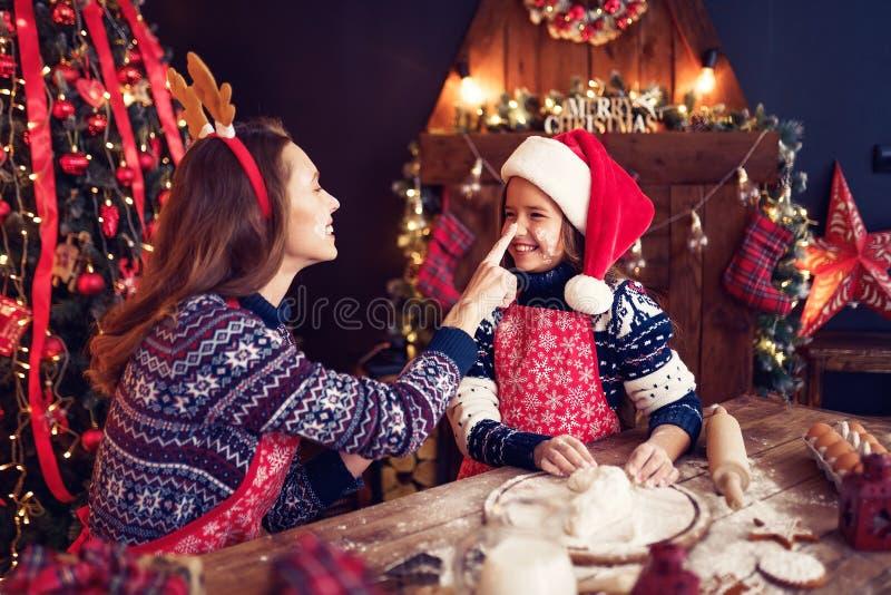 快活的圣诞节节日快乐 烹调圣诞节曲奇饼的母亲和女儿 免版税库存照片