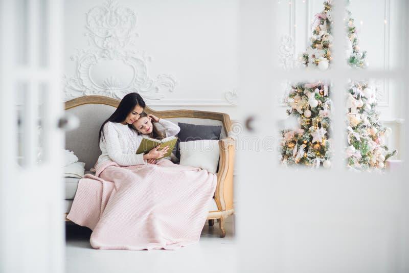 快活的圣诞节节日快乐 相当读书的年轻妈妈对她逗人喜爱的女儿在圣诞树附近户内 免版税库存图片