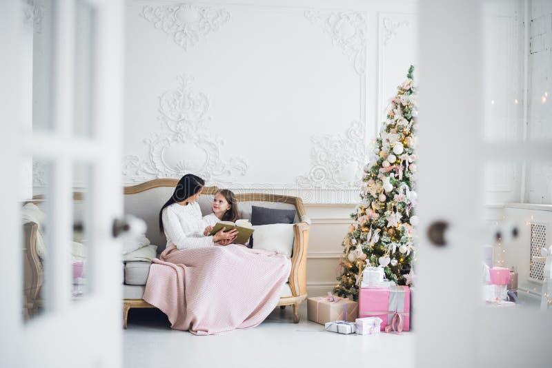 快活的圣诞节节日快乐 相当读书的年轻妈妈对她逗人喜爱的女儿在圣诞树附近户内 免版税库存照片