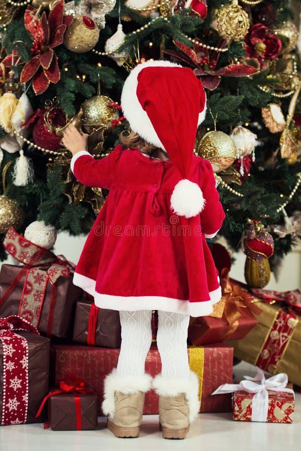 快活的圣诞节节日快乐 逗人喜爱的小孩女孩装饰圣诞树户内 免版税图库摄影
