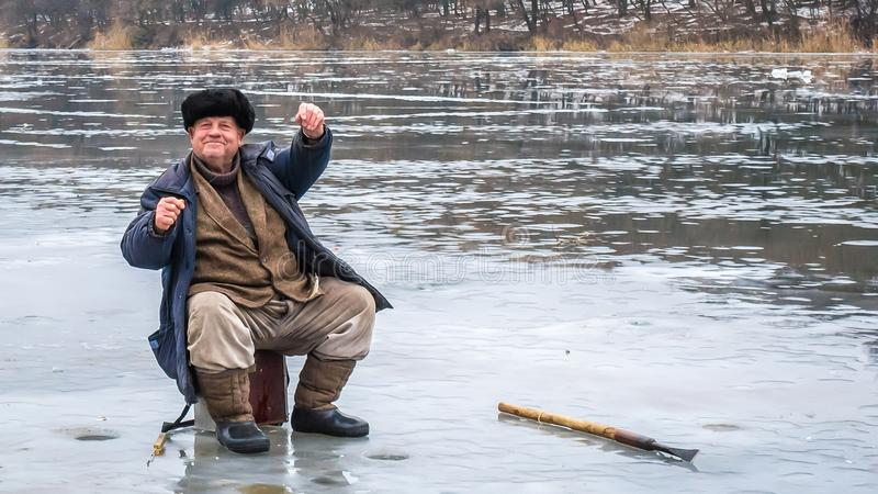 快活的渔夫显示快乐被抓的鱼 在一条冻河的冰的冬天渔 库存照片