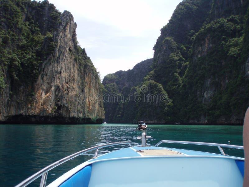 快艇在泰国岩石天际视图清楚的天空的水中 免版税库存图片
