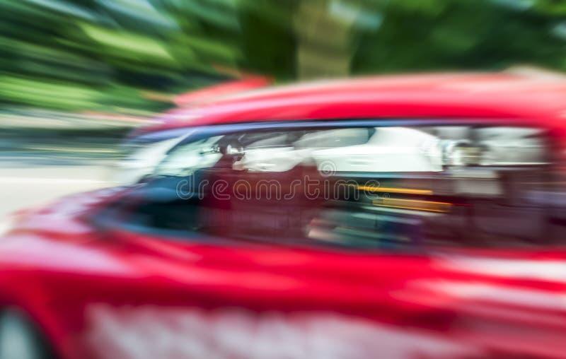 快行红色出租汽车被弄脏的看法在伦敦 库存图片