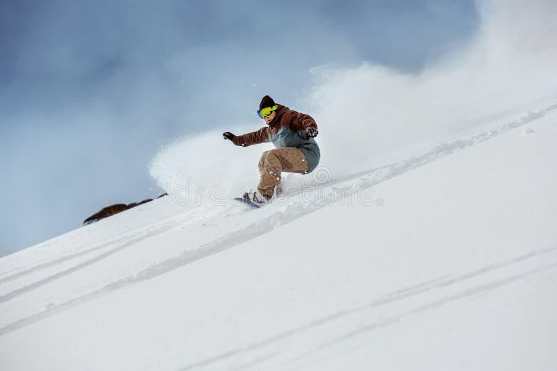 快速地下坡挡雪板滑雪场地外的倾斜 库存照片