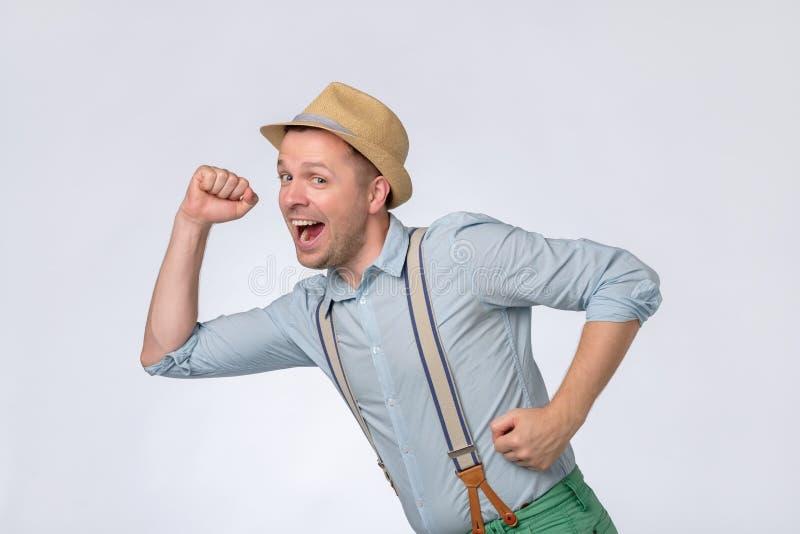 快速地跑他的夏天帽子的可爱的年轻人收到了了不起的消息 免版税库存图片