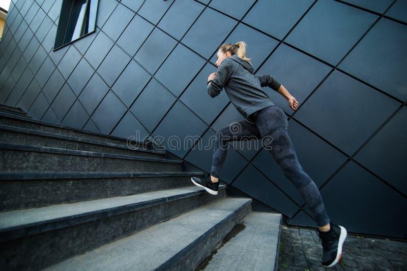 快速地跑台阶楼梯锻炼的女运动员 库存照片