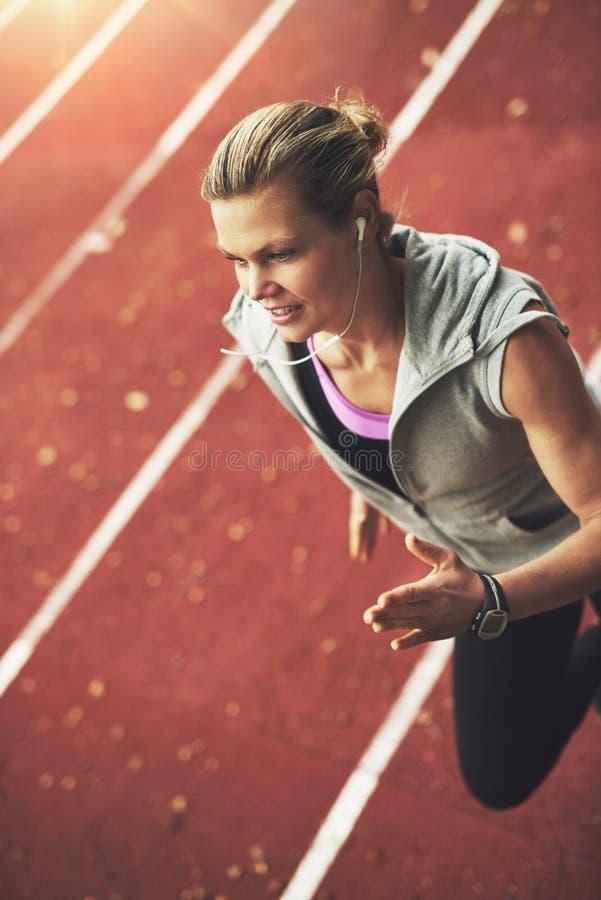 快速地跑在体育场的运动少妇特写镜头  免版税库存图片