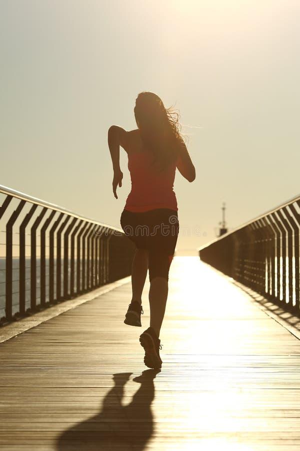 快速地跑在日落的赛跑者剪影 库存照片