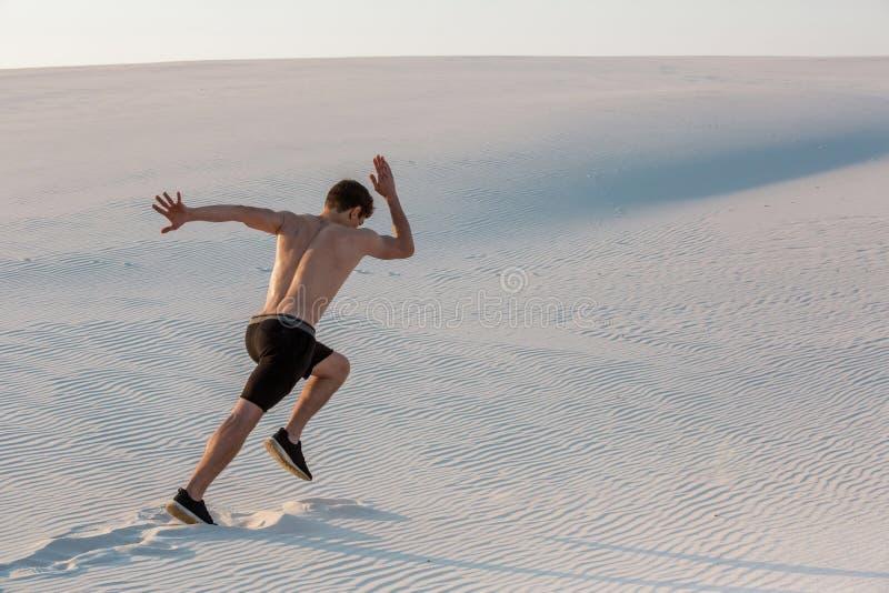 快速地跑在沙子的适合的人 强有力赛跑者训练室外在夏天 库存图片