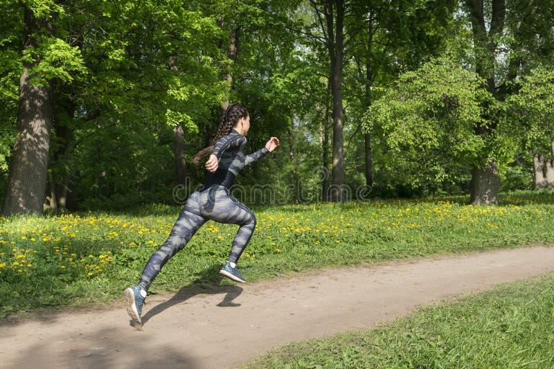 快速地运行通过在绿叶中的公园的卡其色的体育衣裳的1个白深色的女孩 库存图片