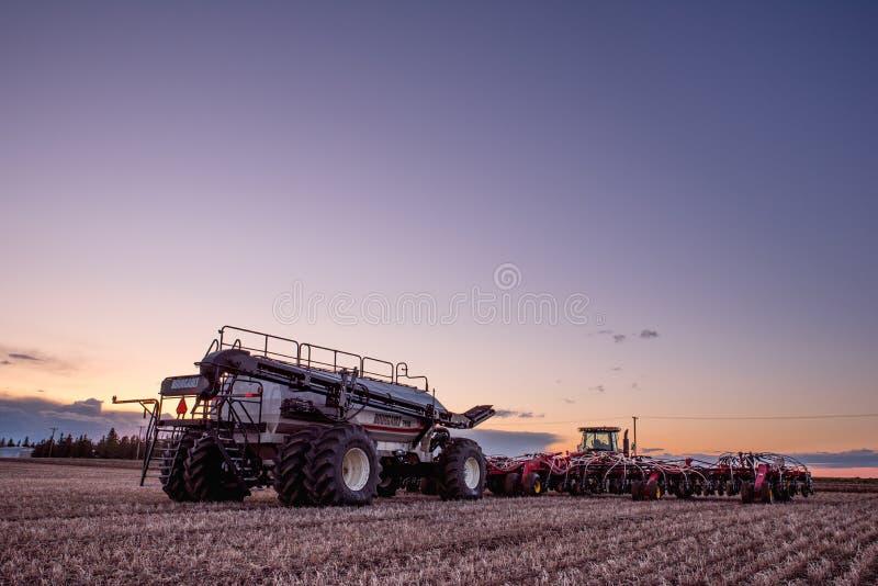 快速潮流,SK/Canada- 2019年5月10日:拖拉机和布尔格播种在领域的飞行训练设备 库存照片
