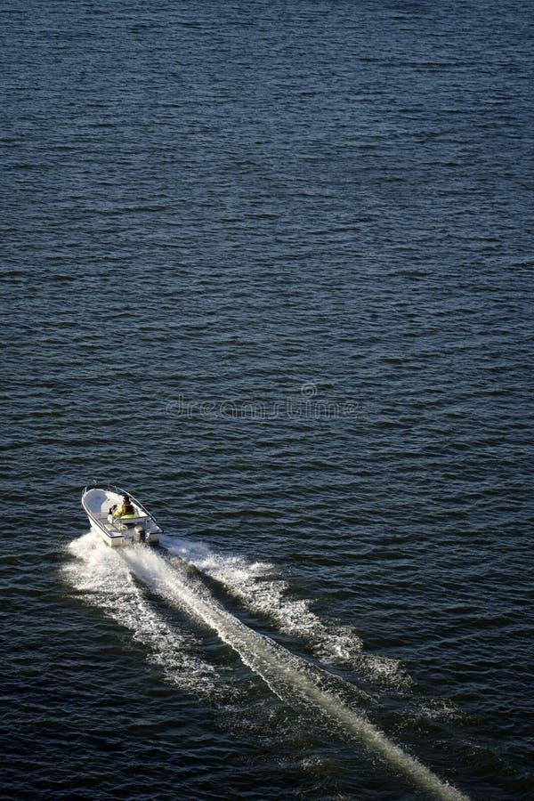 快速的汽艇通过留下泡沫的羽毛的河的黑暗的水冲 免版税库存图片