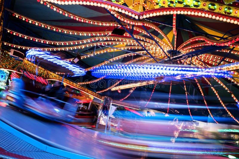 快速的游艺集市乘驾转盘在圣诞节市场上,与被弄脏的行动,抽象背景,拷贝空间的长的曝光 库存图片