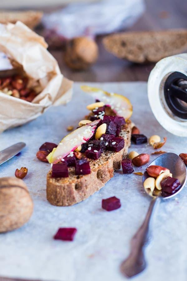 快餐三明治用烤甜菜、坚果、梨和芝麻 图库摄影
