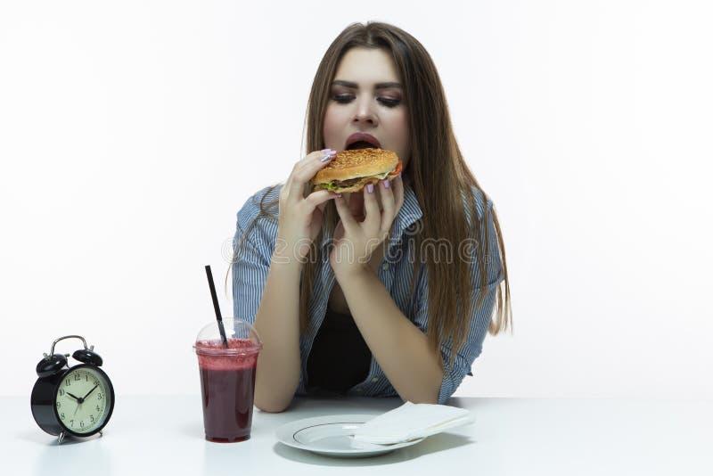 快餐和吃概念 年轻白种人女性用汉堡包和杯红色圆滑的人在演播室 摆在镶边衬衣 免版税库存照片