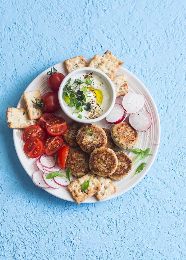 快餐板材 花椰菜丸子、蕃茄,萝卜,面筋自由,薄脆饼干和调味汁 健康快餐素食主义者 免版税库存照片