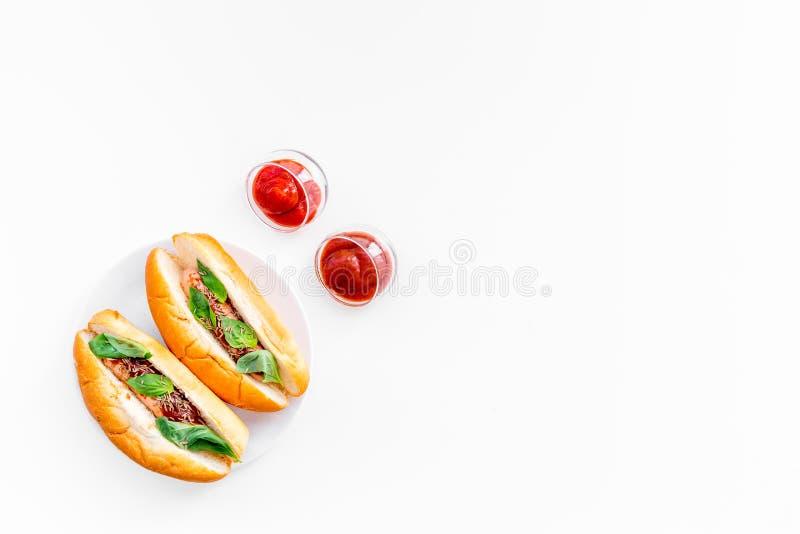 快餐概念 做新热狗和家 热狗的在蕃茄sause附近的小圆面包用freid香肠和蓬蒿在白色 免版税库存照片