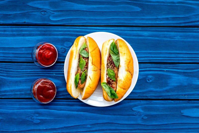 快餐概念 做新热狗和家 热狗的在蕃茄sause附近的小圆面包用freid香肠和蓬蒿在蓝色 免版税库存照片