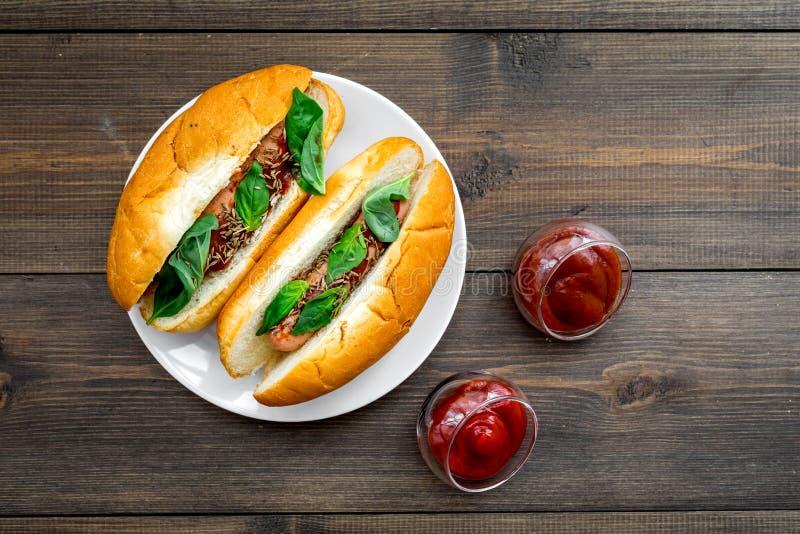 快餐概念 做新热狗和家 热狗的在蕃茄sause附近的小圆面包用freid香肠和蓬蒿在黑暗 库存照片
