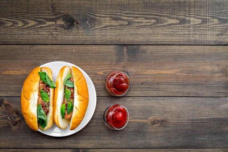 快餐概念 做新热狗和家 热狗的在蕃茄sause附近的小圆面包用freid香肠和蓬蒿在黑暗 免版税库存图片