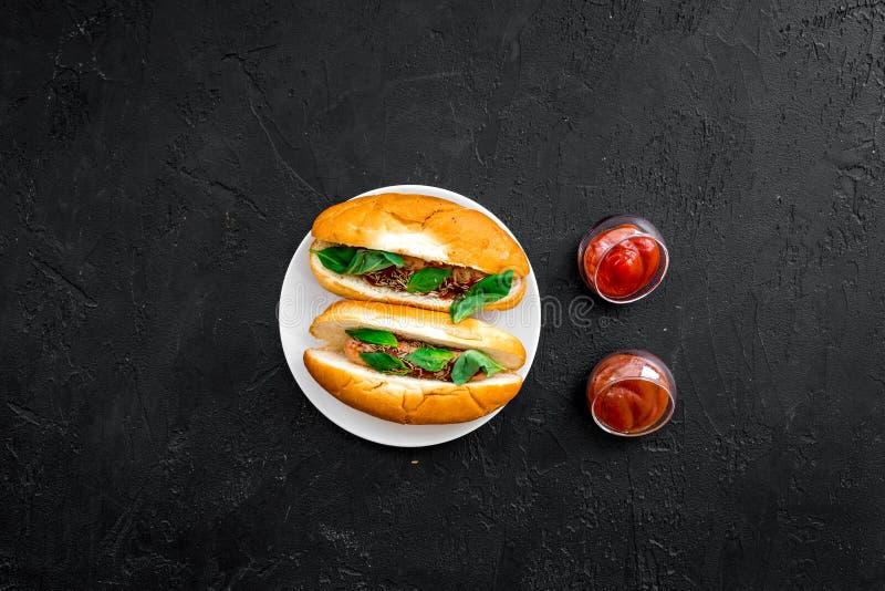 快餐概念 做新热狗和家 热狗的在蕃茄sause附近的小圆面包用freid香肠和蓬蒿在黑色 库存图片