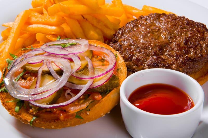 快餐汉堡包和炸薯条在一块白色板材 免版税库存图片