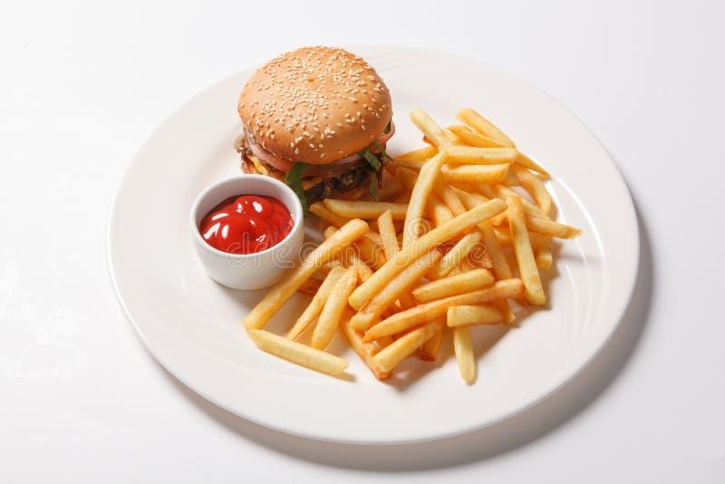 快餐汉堡包和炸薯条在一块白色板材 库存图片