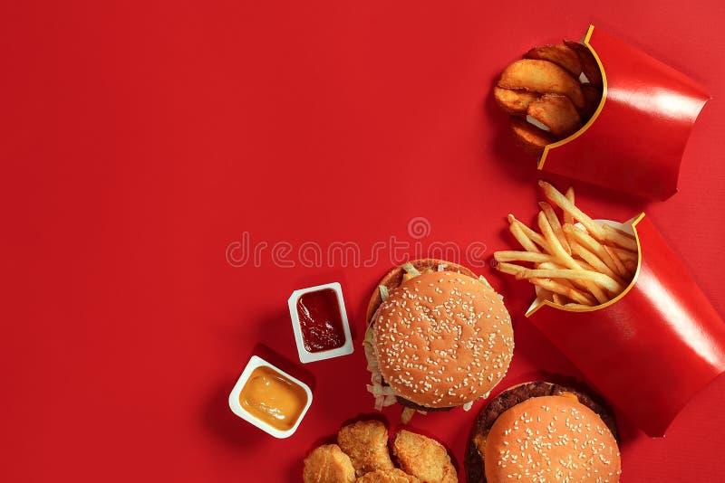 快餐盘顶视图 肉汉堡、土豆片和矿块在红色背景 外带的构成 免版税库存图片