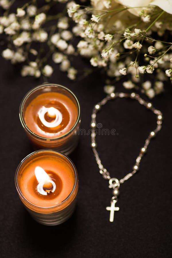 念珠成串珠状与两弄脏了橙色蜡烛和小花,黑背景,在看法上 免版税图库摄影