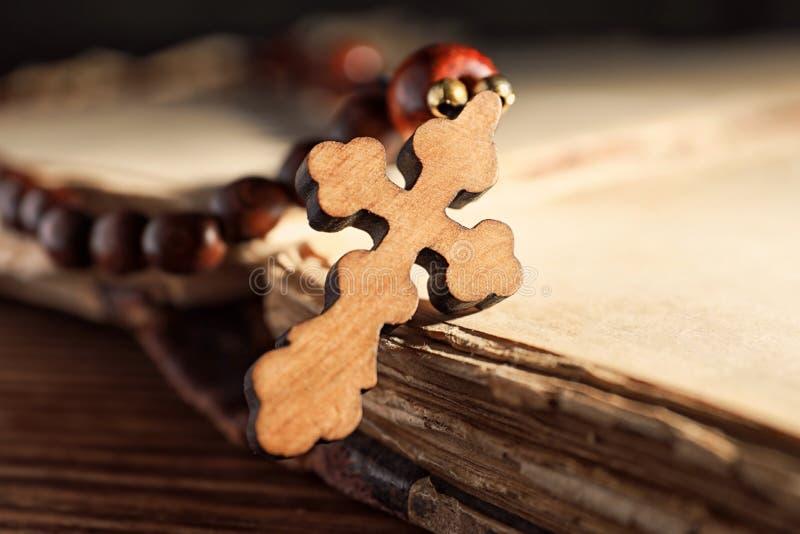 念珠成串珠状与在旧书的木十字架 库存图片