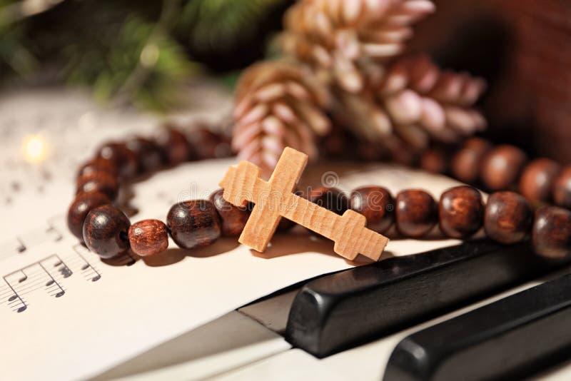 念珠成串珠状与木十字架和音乐纸张 库存图片