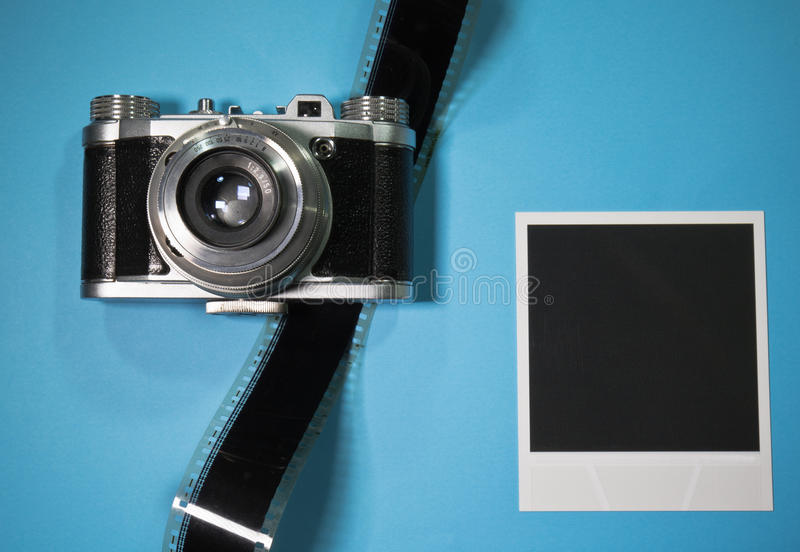 怀乡在蓝色背景的概念空白立即照片框架与与影片小条的老减速火箭的葡萄酒照相机 免版税图库摄影