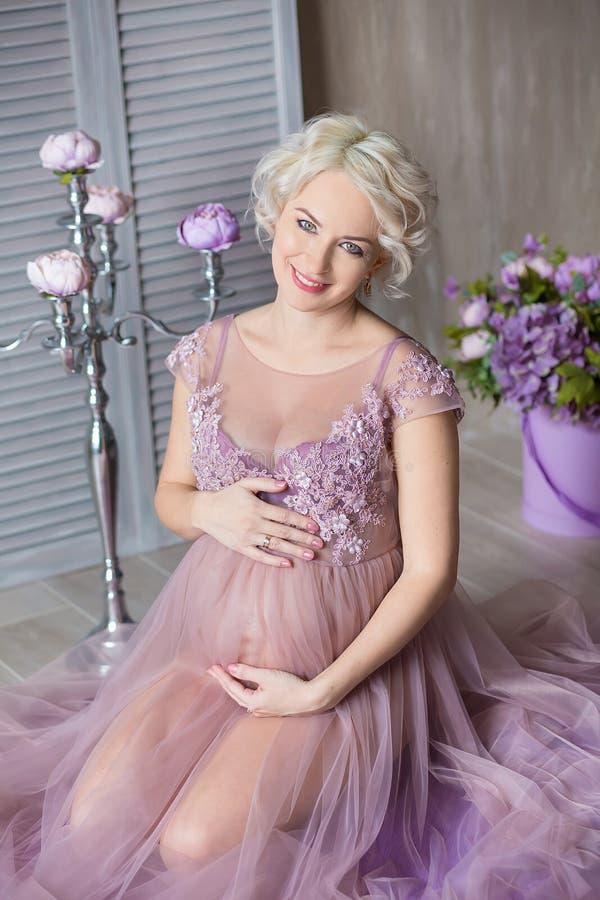 怀孕、母性和愉快的未来母亲概念-通风紫罗兰色礼服的孕妇有反对五颜六色的花束花的 库存图片