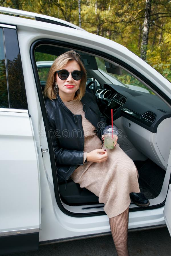 怀孕、母道和幸福 时髦的年轻怀孕的女性有休息她的汽车,坐在白色汽车 美丽的妇女 库存照片