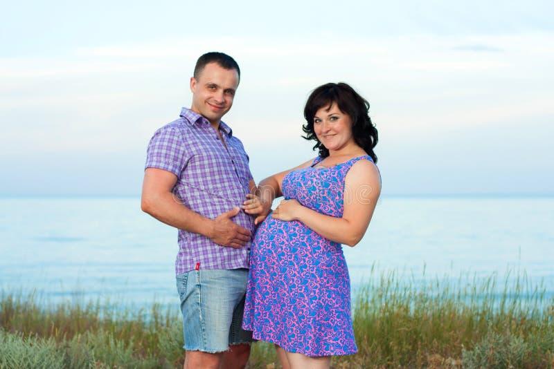 怀孕。在海滩的年轻爱恋的夫妇。 免版税库存图片