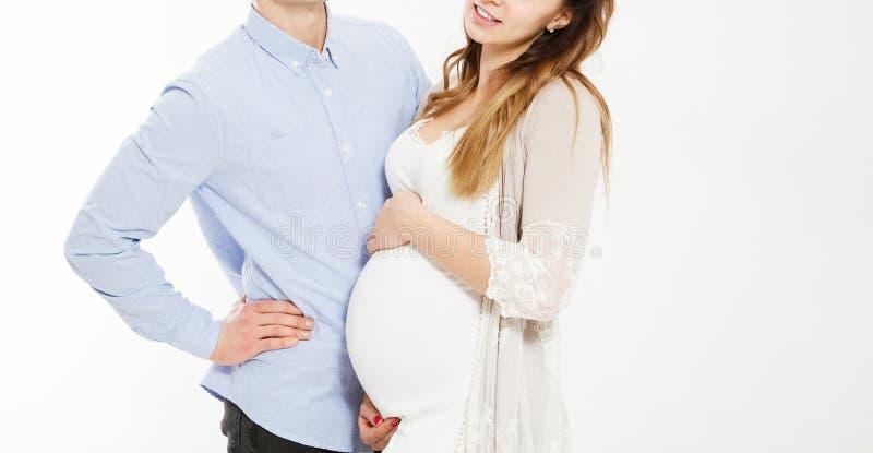 怀孕和人概念-拥抱他怀孕的妻子的愉快的人 免版税库存照片