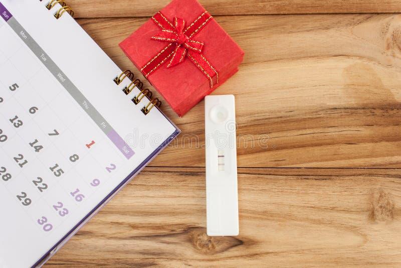 怀孕和日历红色礼物盒在一张木桌上 免版税库存图片