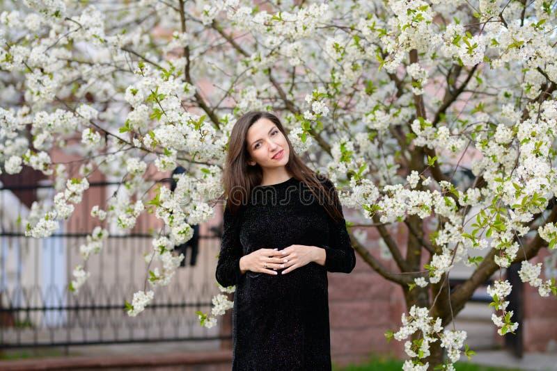 怀孕在夏天 美丽的孕妇 一个年轻母亲的时兴的年轻父母、花和幸福 免版税库存图片