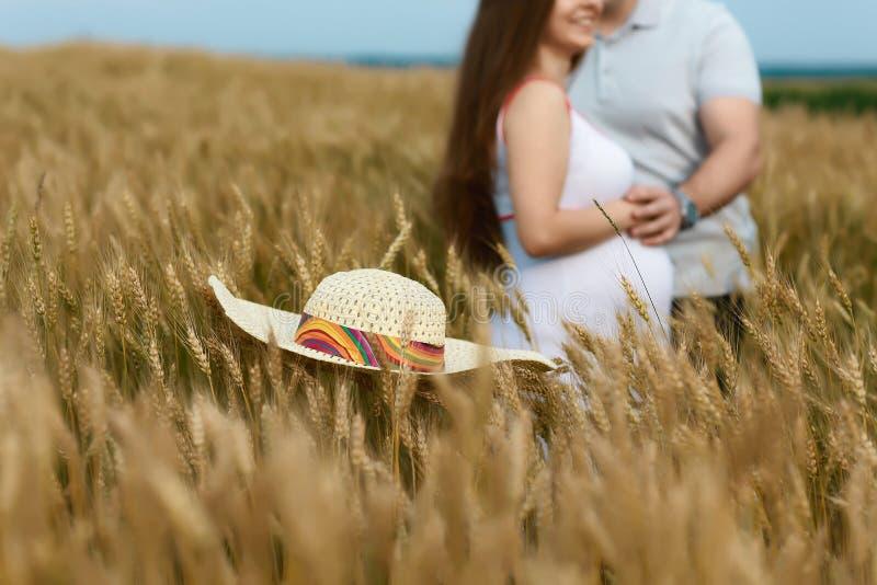 怀孕概念 男人和孕妇领域的到选择聚焦里 婴孩等待 婴孩夫妇愉快等待 免版税库存图片