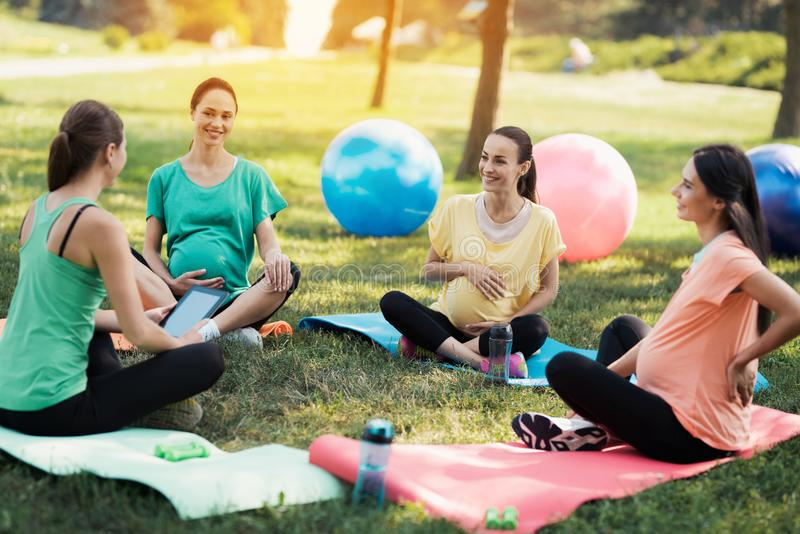 怀孕瑜伽 一位女性教练员在走向瑜伽的三名孕妇前面坐 图库摄影
