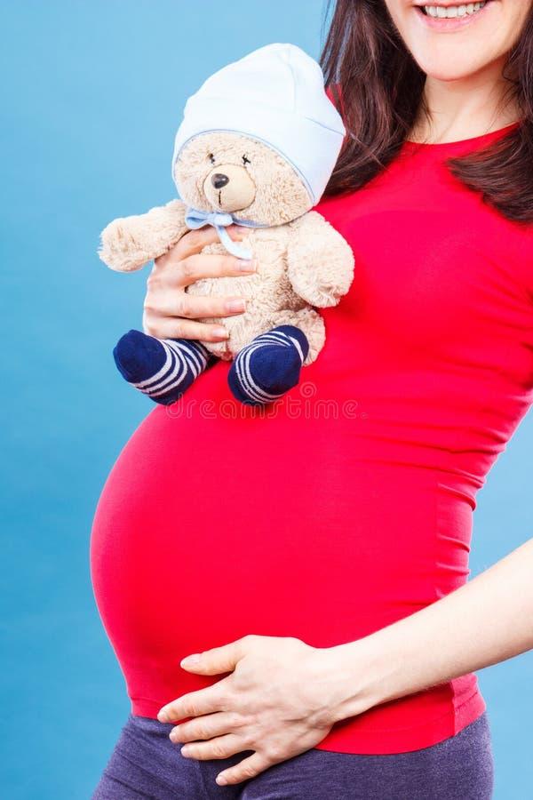 怀孕的举行的玩具熊的妇女在她的腹部,玩具孩子的和期望婴孩概念的 库存照片