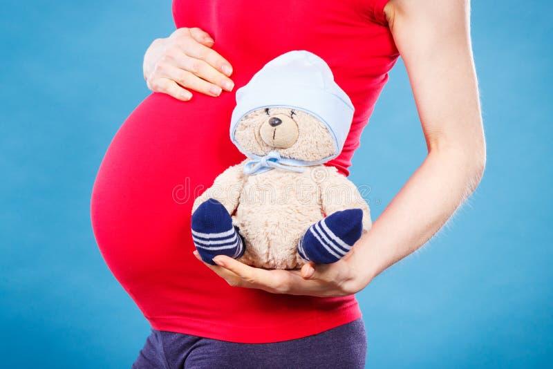 怀孕的举行的玩具玩具熊的妇女,期望为婴孩概念 免版税库存照片