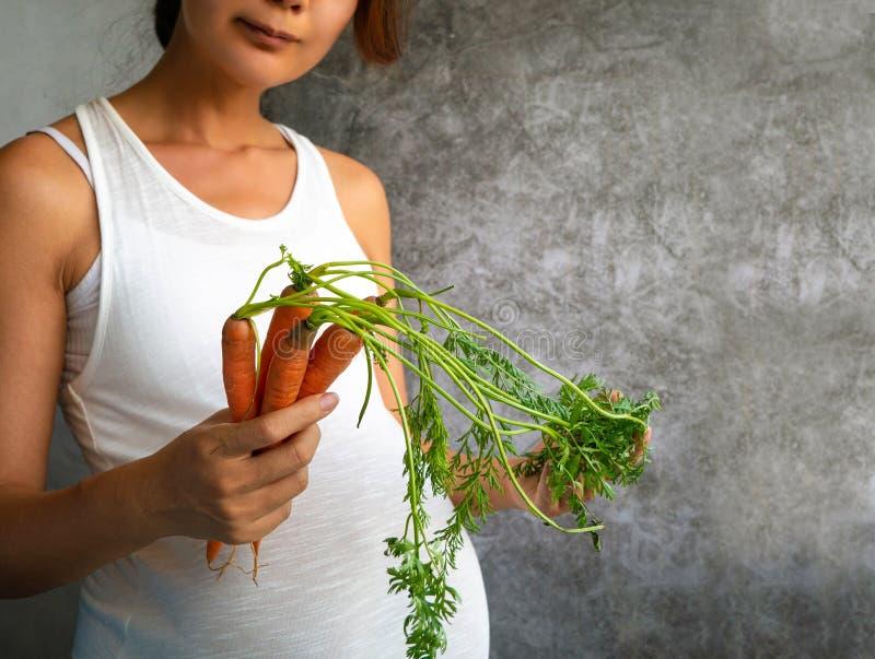 怀孕的亚洲妇女藏品束红萝卜 免版税库存照片